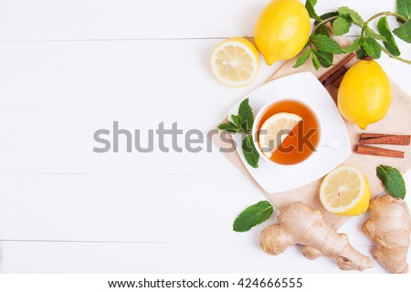 Cup of tea with lemon, mint and ginger on a white wooden background. Top view with copy space