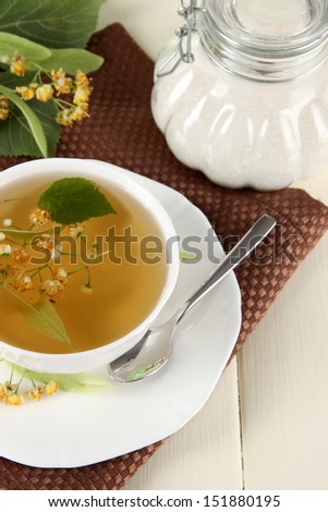 Cup of tea with linden on napkin on   wooden table - stock photo