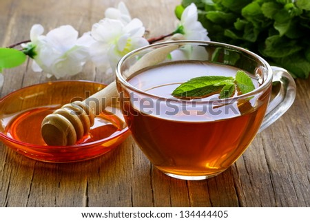 cup of tea with mint and honey on a wooden table - stock photo