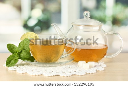 Cup of tea with mint and lime on table in room - stock photo