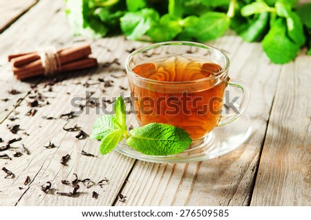 cup of tea with mint leaves on a wooden table - stock photo
