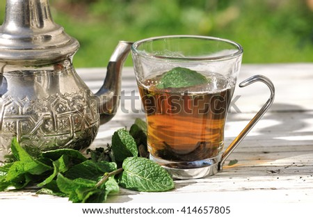 cup of tea with mint leaves on garden table - stock photo