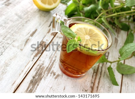 cup of tea with mint on old wooden boards - stock photo