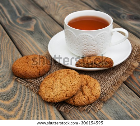 Cup of tea with oatmeal cookies on a wooden background - stock photo