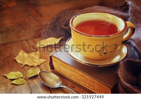 Cup of tea with old book, autumn leaves and a warm scarf on wooden table  - stock photo