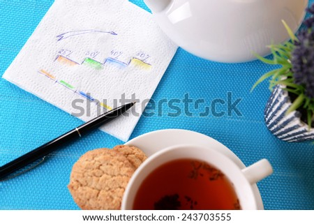 Cup of tea with pen and business notes on napkin on table with turquoise mat background - stock photo