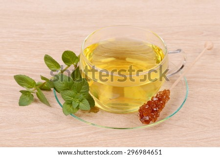 Cup of tea with peppermint and candis - stock photo