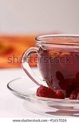 Cup of tea with raspberry syrup and some raspberries