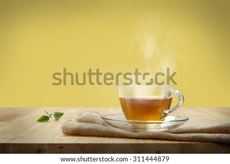 Cup of tea with sacking on the wooden table and yellow background - stock photo