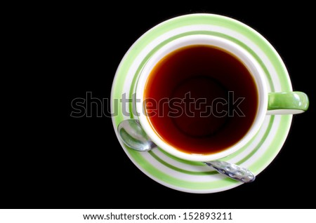 Cup of tea with spoon on black isolate background .  - stock photo