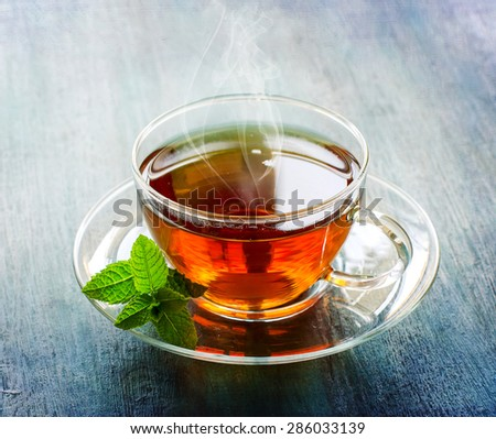 Cup of tea with steam, healthy drink, leaf of mint on dark rustic copy space background - stock photo