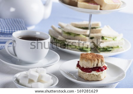Cup of tea with sugar cubes and scones, cucumber sandwiches in the background - stock photo