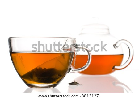 Cup of tea with tea bag inside with a teapot in the background - stock photo