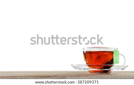 Cup of tea with tea bag on wooden background against grey background - stock photo