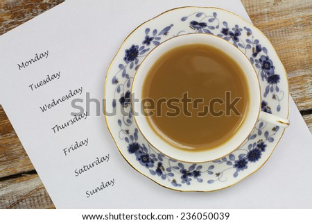 Cup of tea with weekdays listed on white paper  - stock photo