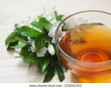 Cup of tea with white flowers on rustic wooden background