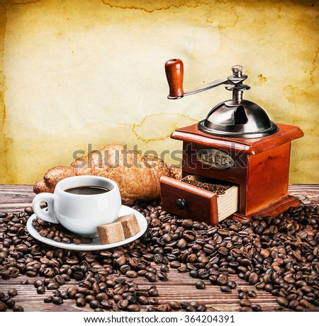 cup of warm coffee and coffee grinder on a wooden table - stock photo