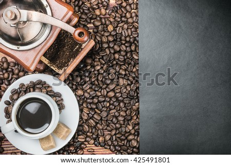 cup of warm coffee and coffee grinder on a wooden table. black paper for text - stock photo