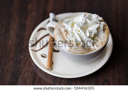 Cup of whipped cream Vienna coffee with cinnamon stick - stock photo