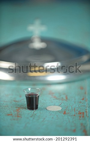 Cup of wine and wafer on vintage table - focus on foreground with shallow depth of field - stock photo