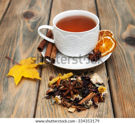 Cup of winter tea and dry herbal tea on a wooden background
