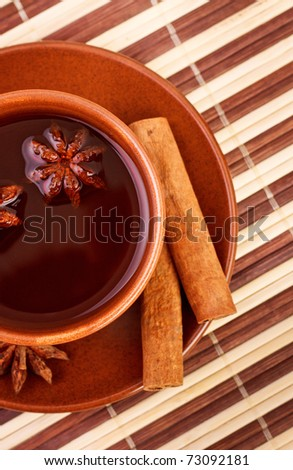 cup of winter tea with cinnamon and star anise on bamboo napkin - stock photo