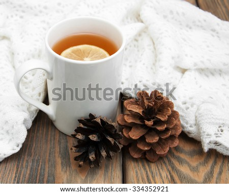 Cup of winter tea with scarf on a wooden background - stock photo