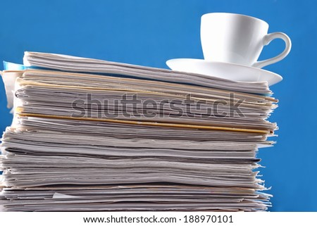 Cup on a pile of papers against a blue background - stock photo