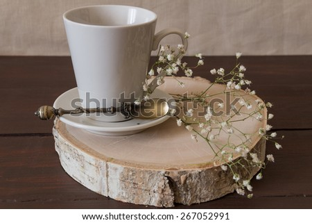 Cup on a wood cut and flowers - stock photo