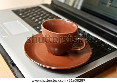 Cup on laptop keyboard - stock photo