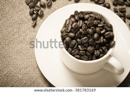 Cup, saucer and coffee beans on a burlap background. Selective focus. Toned.