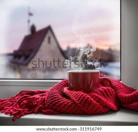 cup with a hot drink on the windowsill in the background of a winter city. Focus on the edge of the cup - stock photo