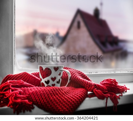 cup with a hot drink on the windowsill in the background of a winter city. To use the greeting for Valentine's Day - stock photo