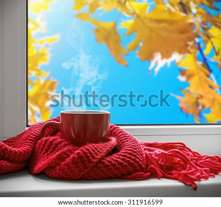 cup with a hot drink on the windowsill on the background of autumn leaves. Focus on the upper edge of the cup - stock photo