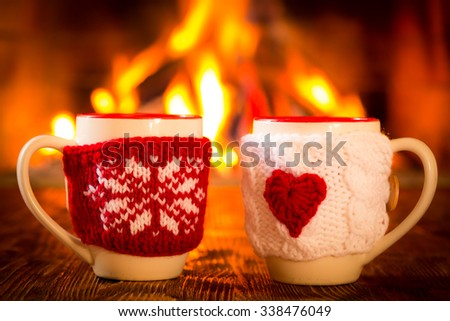 Cup with Christmas and Valentine ornament near fireplace. Winter holiday concept. Couple, love, Valentine's day - stock photo