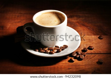 cup with coffee and coffee beans on  wooden table - stock photo