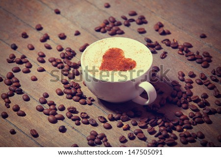 Cup with coffee and shape of the cacao heart on it.  - stock photo