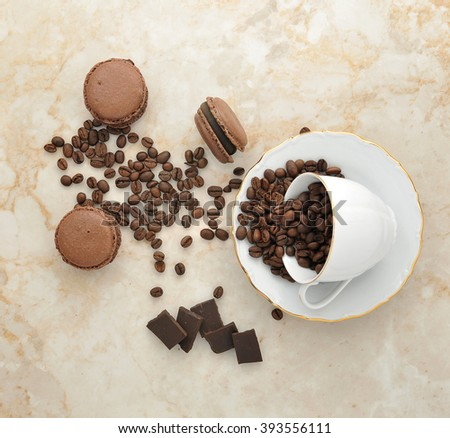Cup with coffee beans and chocolate cake macarons and bits of chocolate on a marble background. top view - stock photo