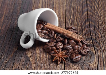 Cup with coffee beans, cinnamon and anise on wooden board - stock photo
