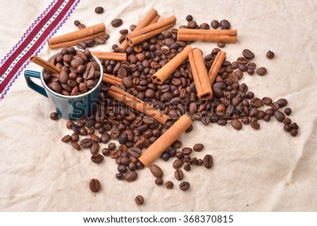 Cup with coffee beans cinnamon stick on jute background. Morning pleasures. Awakening flavors. Selective focus - stock photo