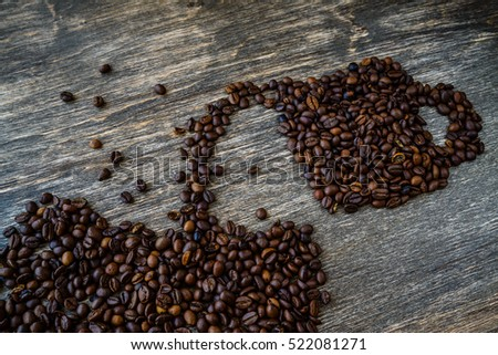 Cup with coffee beans on old wooden background.