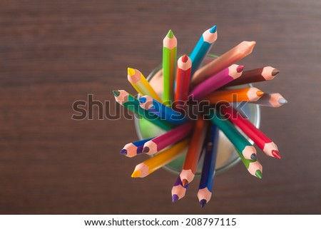 Cup with colorful Pencils on wooden table - stock photo