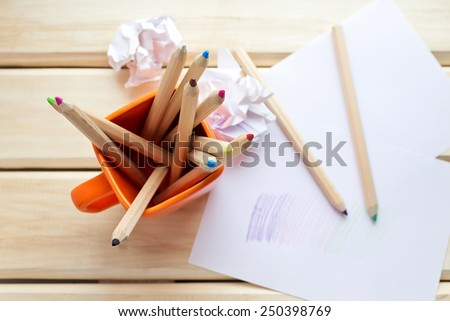 Cup with colorful Pencils on wooden table. Top view - stock photo