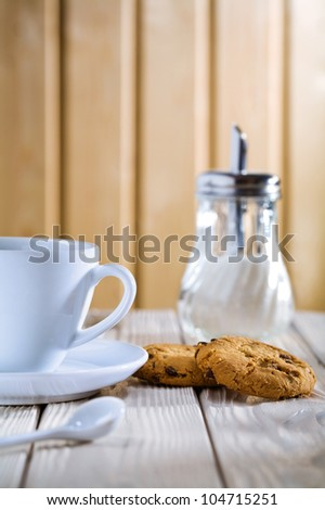 cup with cookies and sugar dispenser on table - stock photo