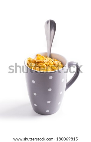 Cup with corn flakes on white background - stock photo