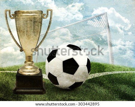 Cup with football and gates on green field - stock photo