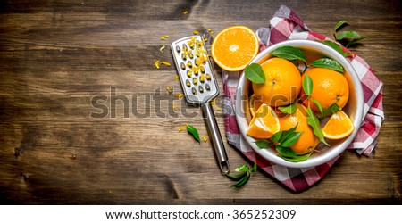 Cup with fresh oranges, zest and grater on fabric. On a wooden table. Free space for text . Top view - stock photo