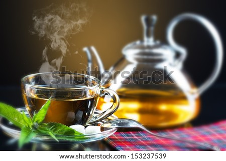 Cup with green tea and green leaves.