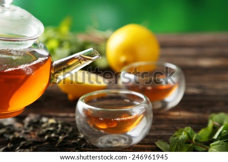 Cup with green tea and teapot on brown wooden background - stock photo