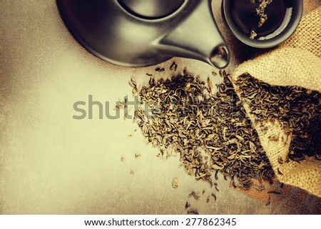 Cup with green tea and teapot on grey background. - stock photo